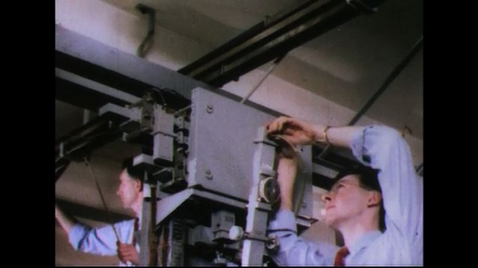 UNITED STATES 1950s: Man adjusts piece of equipment, climbs down / Man adjusts equipment, other man takes notes.