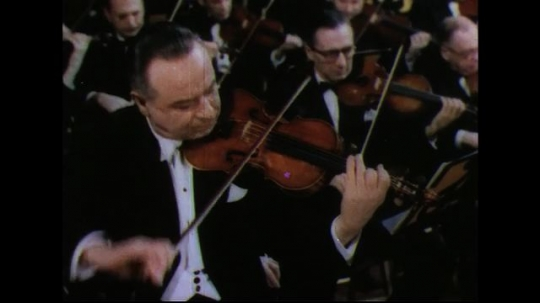 UNITED STATES 1950s: Man playing violin / Violinist with orchestra in background.