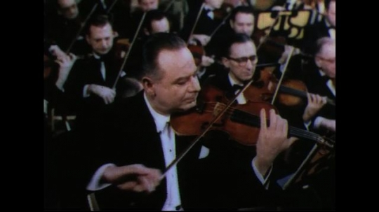 UNITED STATES 1950s: Man playing violin with orchestra in background.