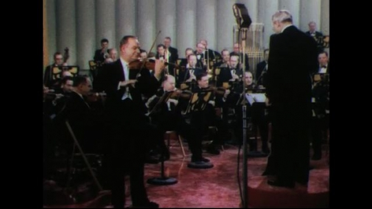UNITED STATES 1950s: Man playing violin, conductor conducting with orchestra in background.