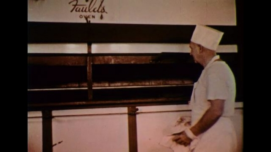 UNITED STATES 1950s: A baker waits for the bread to be baked as milk is processed in a plant.