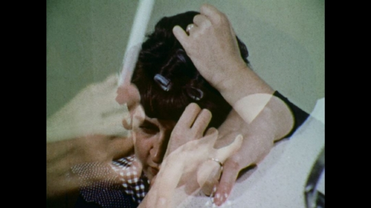 UNITED STATES: 1970s: lady backcombs hair with comb. Lady brushes hair.