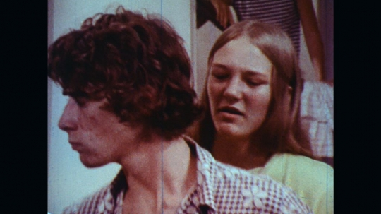 UNITED STATES: 1970s: girl and boy argue at party. Boy takes whisky and bottles from cupboard