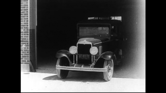 SANTA PAULA- CIRCA 1929: Three cars pull out of a garage, followed by two well dressed older men, who step out onto the sidewalk.