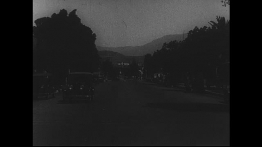 SANTA PAULA- CIRCA 1929: The center of a street lined with large trees, streetlights, and parked cars.  Mountains can be seen in the distance.  A few cars drive toward and past the camera.