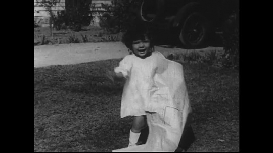SANTA PAULA- CIRCA 1929: A toddler in a dress plays with a newspaper in a front lawn.  At first she stands, but is then seen sitting on a pillow. She eventually rips the paper.