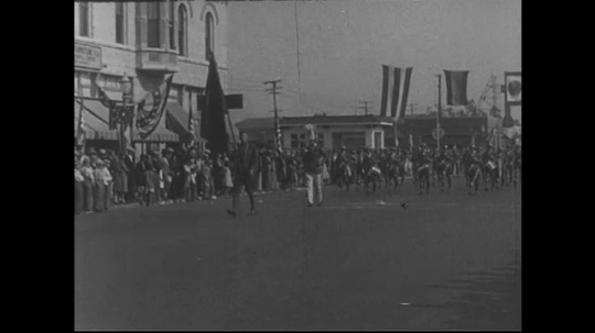 SANTA PAULA- CIRCA 1929: A street parade.  A drum corp marches and plays as spectators watch from the sidewalk.