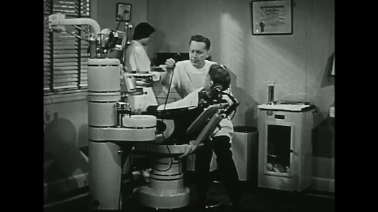 UNITED STATES 1940s-1950s :A young boy washes his mouth after a dentist finishes doing a procedure.