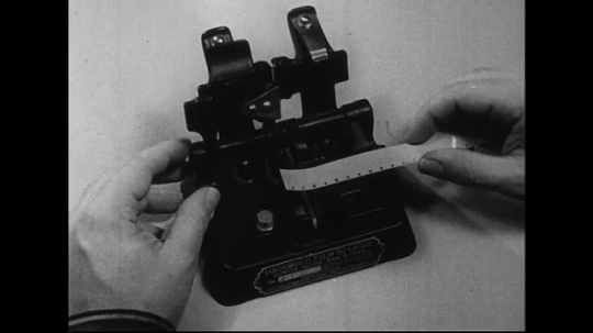 1940s-1960s : Damaged film tape is placed in a splicer and cut off.