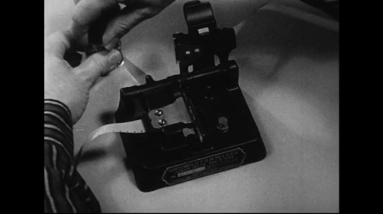 1940s-1960s : After cement is applied to a piece of tape on the left side of a splicer, two pieces are joined together.