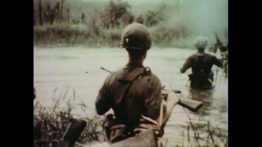 VIETNAM 1960s: Soldiers wade through river / Soldier wades past camera.