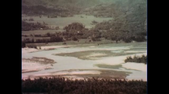 VIETNAM 1960s: View of field, zoom out to officers talking to soldiers.