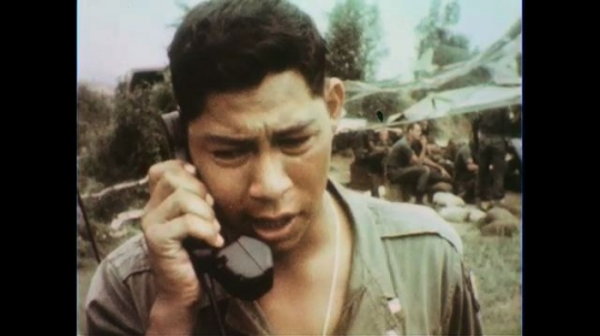 VIETNAM 1960s: Close up, soldier on field phone / Soldier looks through gun sight, soldiers load gun / Field gun fires / Soldier pulls rope across river.