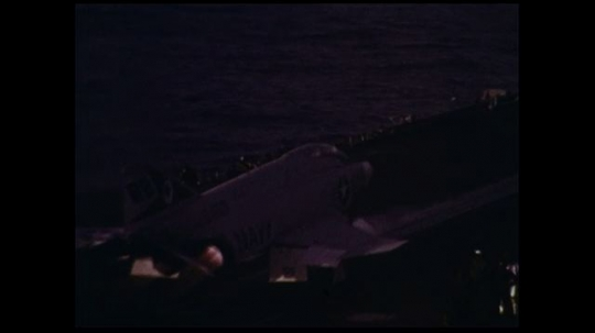 UNITED STATES 1970s: As one warplane takes off from a war ship's deck, another one lands.