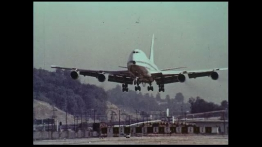 UNITED STATES 1970s: An airplane lands on the runway of an airport.
