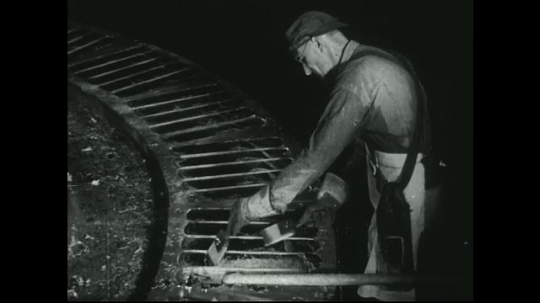 UNITED STATES: 1940s: factory operator scoops metal from racks on machine. Man skims molten metal with paddle