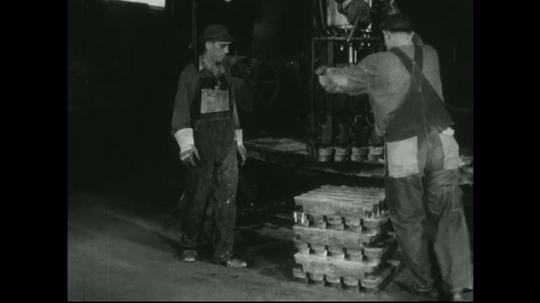 UNITED STATES: 1940s: man stamps brand on metal blocks with machine. Worker turns metal block over. Vehicle picks up blocks of metal and moves them.
