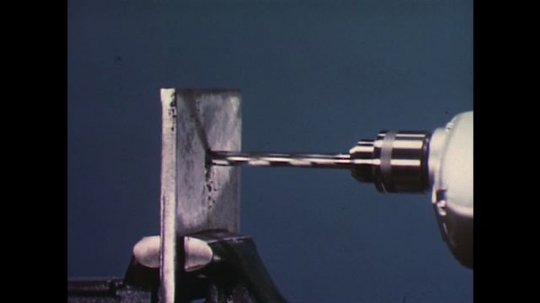 UNITED STATES 1960s: Close up of drill going through metal / Hands push drill through metal.