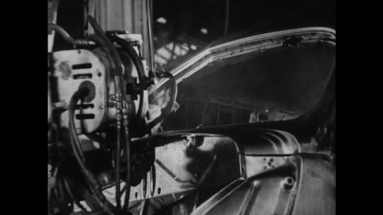 UNITED STATES 1930s-1940s : A factory worker uses a suspended welder to weld exterior car parts together.