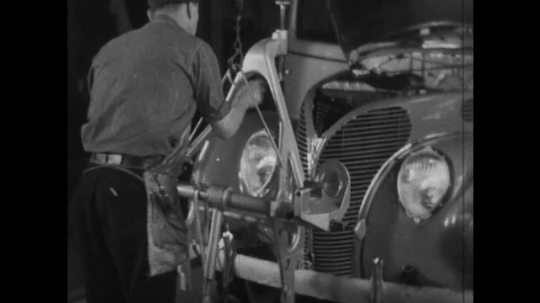 UNITED STATES 1930s-1940s : Factory worker affixes a hanging metal bar to the front of a car and tightens its headlights. An employee is seen driving a completed car out of the factory assembly line.