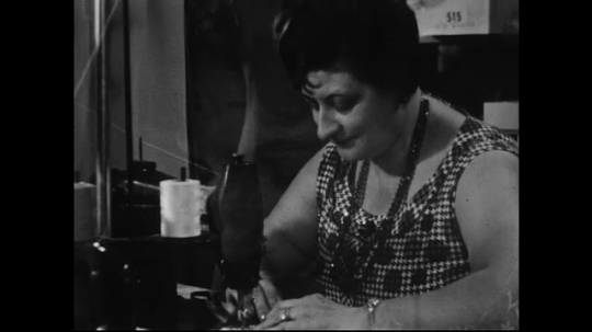 AMERICA: 1950s: A woman feeds a piece of fabric through a sewing machine.