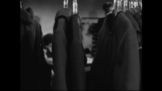 AMERICA: 1950s: A rack of men's jackets pulls away to reveal a panel of clothing buyers who look at a dress a man holds up to them. The buyers converse and take notes.