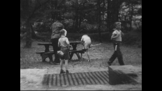 UNITED STATES 1940s: Family walks away from picnic table, boy lingers, looks at fire pit.