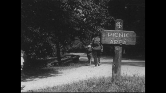 UNITED STATES 1940s: Family walks away from picnic area, end credit, fade to black.
