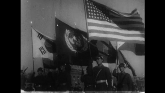 UNITED STATES 1950s: The South Korean flag waves with the United Nations and American flags as troops walk in the fields.