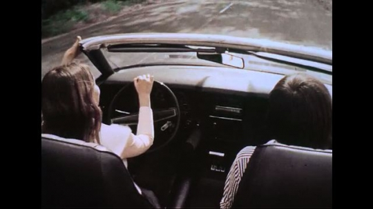 AMERICA- CIRCA 1970: A young woman, accompanied by a young man, drives her top-down black convertible down a street. A POV perspective, from the front of a car, of a highway at dusk.