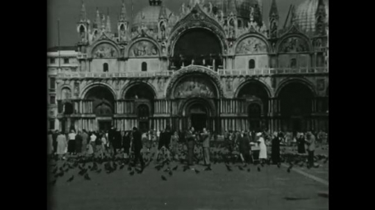 UNITED STATES 1950s: Pigeons roam outside a cathedral in Venice as tractors plow through farmland.