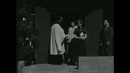 UNITED STATES 1950s: Throngs of people shake hands with a priest as they exit church.