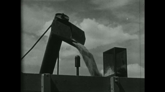 UNITED STATES 1950s: Crop is loaded into a container while an astronomer looks through a telescope into space.