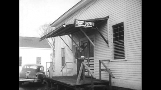 UNITED STATES 1950s: Boy walks out of post office / Post office sign / US State Department sign / Man and woman review photographs in office.