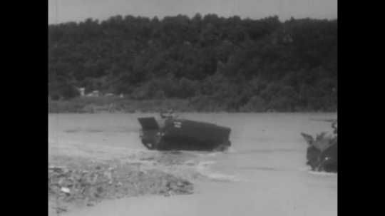 EUROPE, 1950s: Tanks driving along river bed. Army vehicles driving along dust road. Wounded soldier carried on a stretcher.