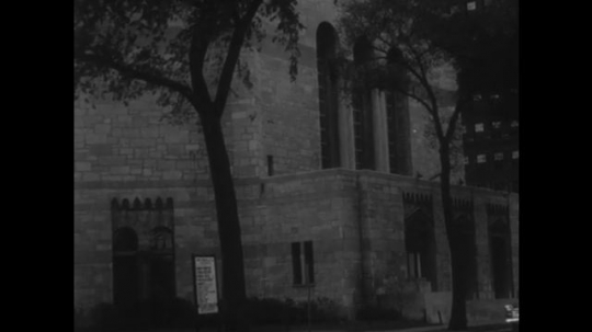 UNITED STATES, 1940s: Cars driving past a church. View towards church spire. Church with tower. Ladies working in a library. Lady reading 'Peace of Mind' book.