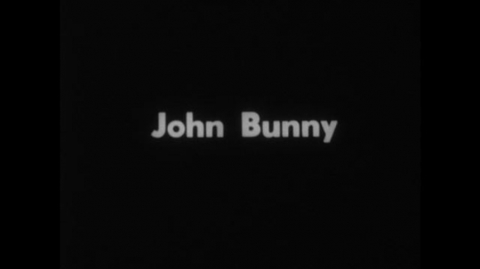 UNITED STATES 1890s: Intertitle / Actor John Bunny puts on coat / Bunny puts on hat, looks in mirror / Intertitle / Alexander Graham Bell talks into camera / Bell with woman and baby.