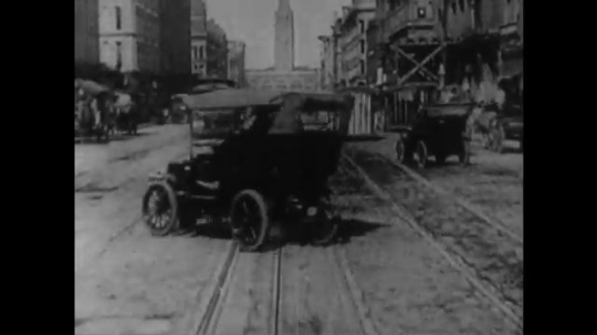 UNITED STATES 1890s: Tracking shot down city street / Intertitle / Tracking shot down street / Intertitle.