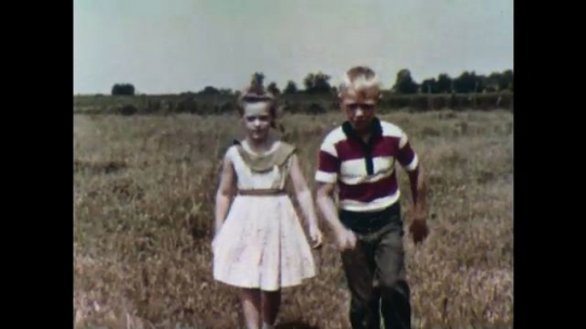UNITED STATES, 1956: Boy and girl pick up a turtle.