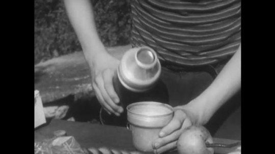 UNITED STATES, 1944: Boy pours milk into a cup and drinks it.