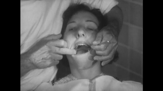 UNITED STATES, 1944: Dentist looks at girl's healthy teeth and children get off of bus.