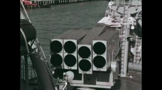 UNITED STATES: 1968: equipment on deck of ship. Ships on ocean. Sailor operates machine on ship