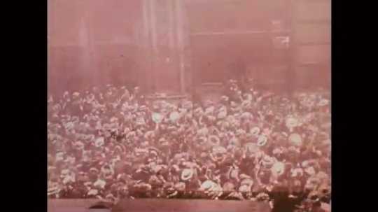 1920s: Large street crowd cheers and waves hats. People in balconies wave flags.