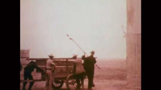 1920s: Men lift pole, box from cart. Men, wood stilts. Men watch from outpost. Rocket launches, explodes in sky. Man with headset turns control panel switch. Man records radio. Truck drives by plane.