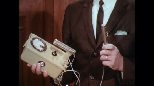 UNITED STATES: 1960s: man holds Geiger counter. Man puts machine on shelf. Man talks to camera.