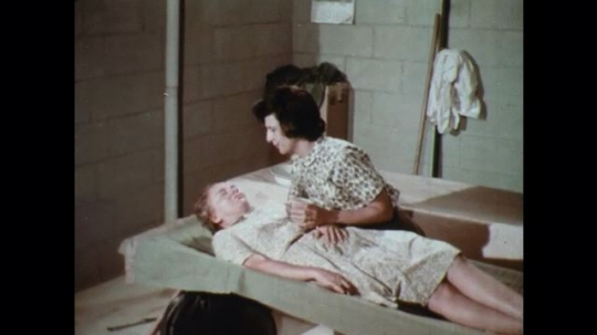 UNITED STATES: 1960s: lady nurses sick woman. Lady gives water to lady.