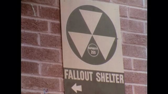 UNITED STATES: 1960s: people inside fallout shelter. Fallout shelter sign. Civil defense poster