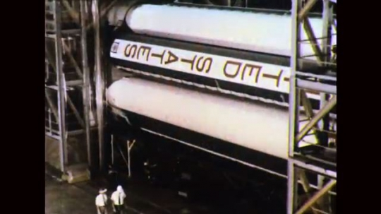 UNITED STATES: 1960s: United States logo on space rocket. Man walk next to rocket. Men work on rocket.