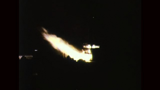 UNITED STATES: 1960s: flames under rocket on launch pad at night.