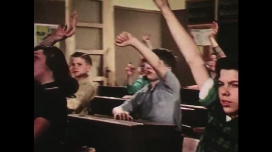 UNITED STATES: 1950s: students raise hands in classroom. Boy smiles at desk. Boy comes to front of class. Boy frowns. Girl smiles.